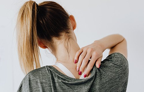 Woman touching back of neck in pain