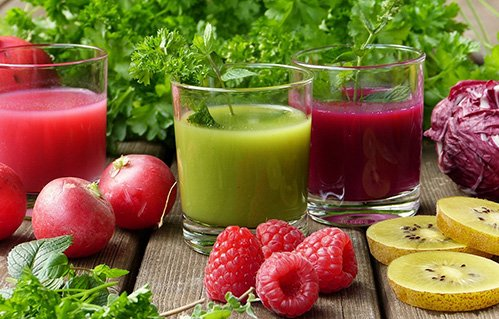 S selection of fruits and herbs surround two glasses of smoothie drinks