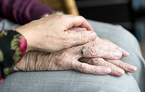 Closeup of woman's hand over an elderly person's hands