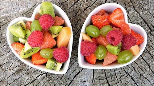 Fruit inside two white heart shaped bowls