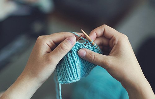 Closeup of hands knitting yarn