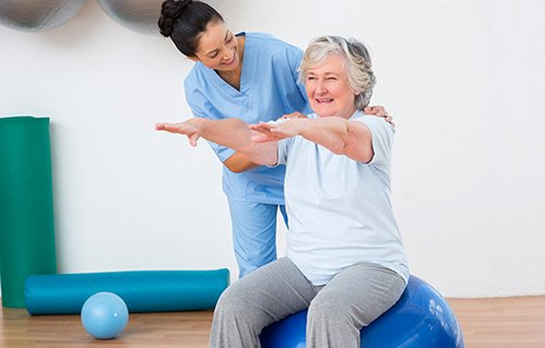 Occupational therapist treats a senior woman on an exercise ball