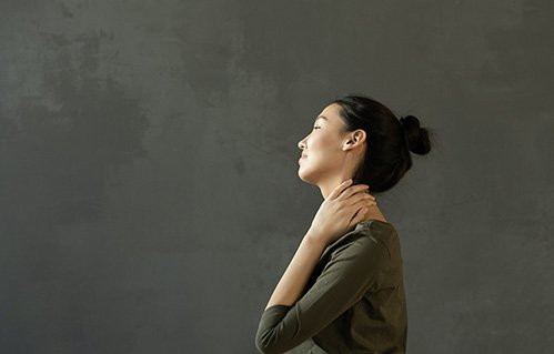 Woman massages her neck
