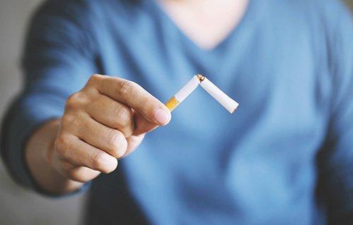 Man displaying broken cigarette