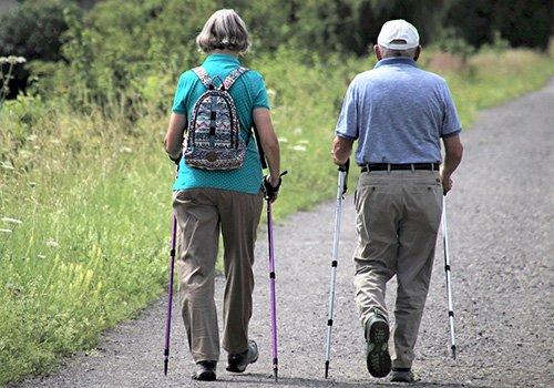 A senior couple walk outside with sticks