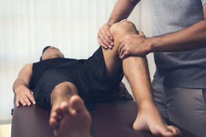 Physiotherapist treats a patient's knee