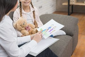 Social worker speaks with child about her drawing