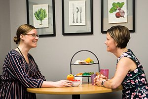 A dietitian speaks with a patient at a table with fruits and vegetables on display