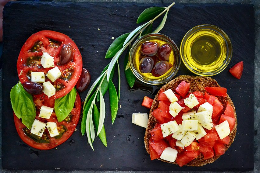 Food on table, watermelon, olives, olive oil, rosemary, sliced tomatoes