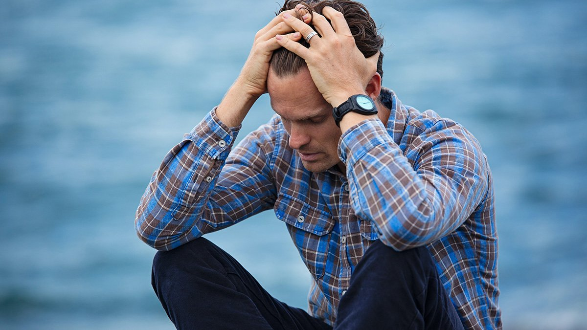 Man crouched in anxious pose