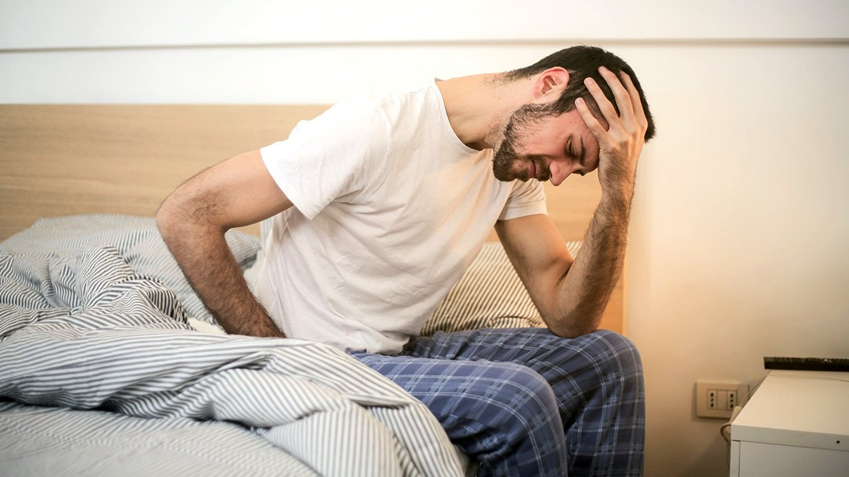Man with insomnia sitting on bed with head in hand