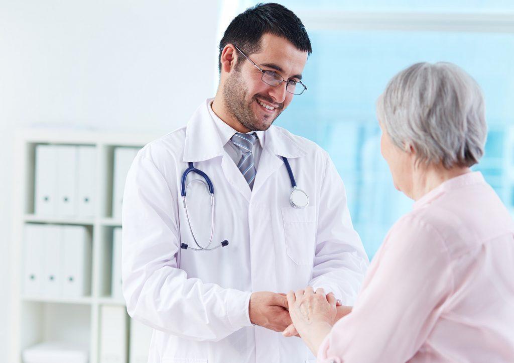 Friendly doctor holds elderly patient's hands